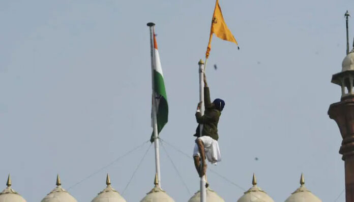A protestor climbs atop the Red Fort to hoist a flag of their own